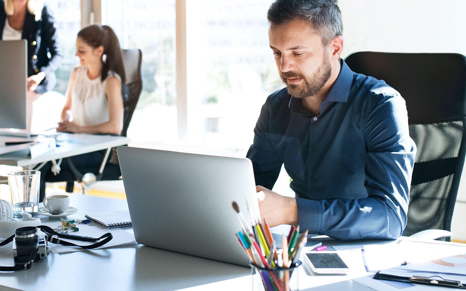man working on laptop in office setting